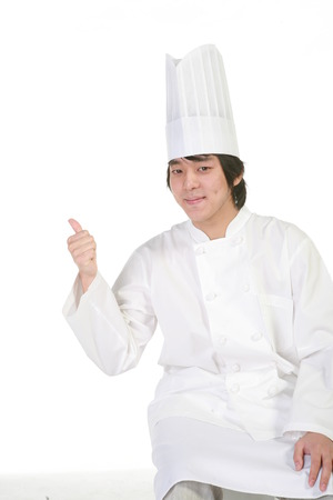 A male patissier with a thumb up as sitting down