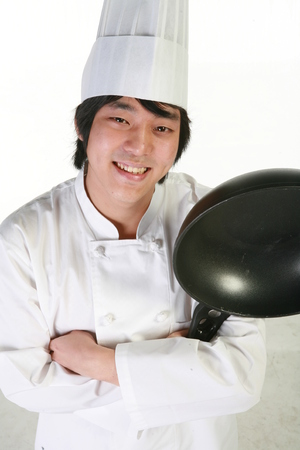 Close up shot of a male patissier holding a frying pan upside down as arms crossed Stock Photo