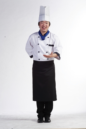 A male cook showing an empty hand to the front