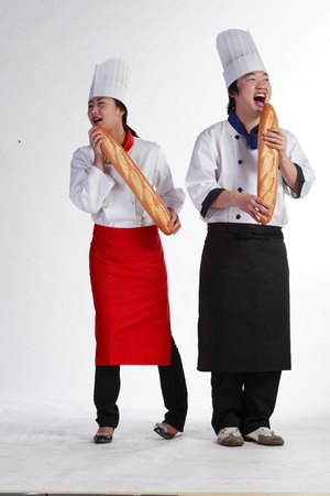 A couple of cooks holding loaves of bread pretending to sing a song Stock Photo