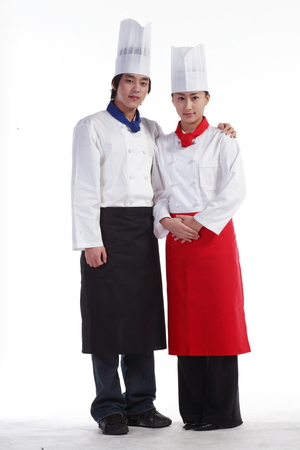 A couple of cooks standing as putting arms around