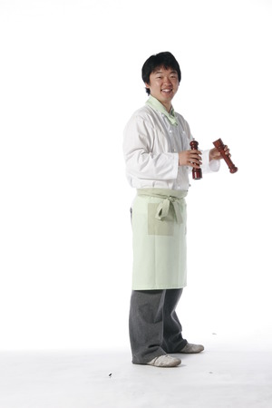 Side shot of a male cook holding a set of salt shaker and pepper shaker in each hand