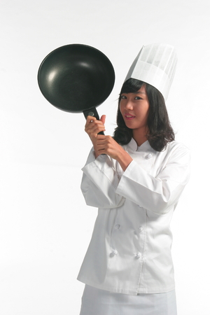 A female cook holding a frying pan by her head Stock Photo