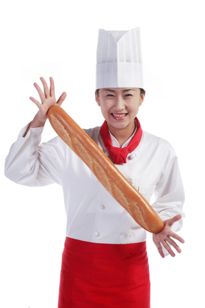 A female cook holding a loaf of bread with open hands