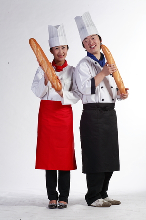 A couple of cooks standing as holding loaves of bread in hand