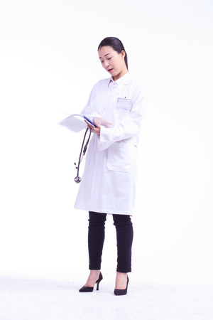 looking for job: A female doctor looking at a chart as holding a stethoscope in hand