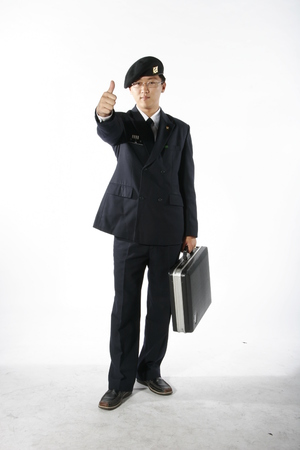 disciplined: A male soldier wearing glasses showing a thumb up as holding a briefcase