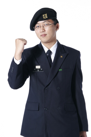 A male soldier wearing glasses in a cheering pose showing a fist up in the air