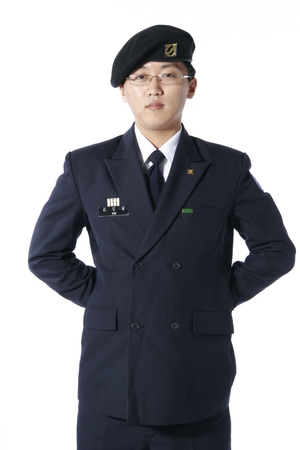 disciplined: Front shot of a male soldier wearing glasses putting hands behind the back as in at ease