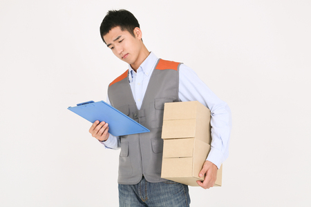 A delivery man checking the chart as holding boxes of shipments in arm