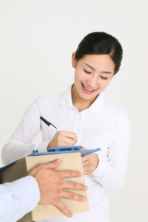 A female recipient signing on the sheet with toothy smile