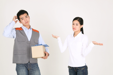 A delivery man scratching his head while the receiving woman shrugging shoulders
