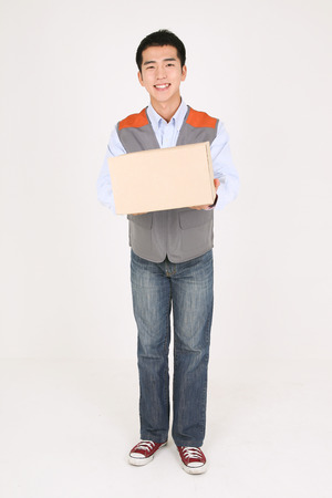 completion: A delivery man holding a box of shipment with toothy smile
