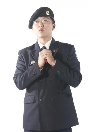disciplined: A male soldier wearing glasses putting both hands together in front of the chest Stock Photo