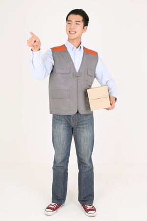 A delivery man pointing with index finger as holding a box of shipment