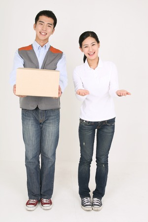 A delivery man holding a shipment with a female recipient by his side
