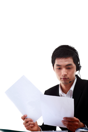 customer service representative: A male telemarketer reading paper report Stock Photo