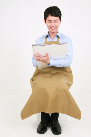 Full shot of a male artist drawing on a sketchbook as holding it in arms Stock Photo