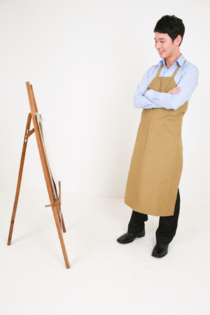A male artist standing in front of the easel as crossing arms