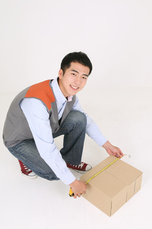A delivery man measuring a box as sitting down Stock Photo