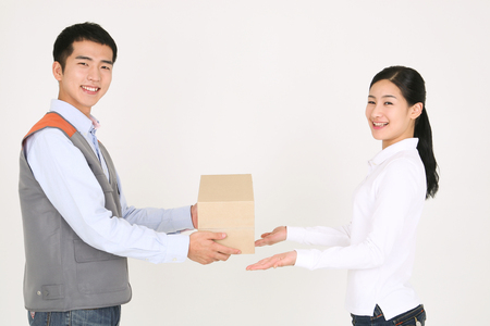 A delivery man handing over a package to a female recipient