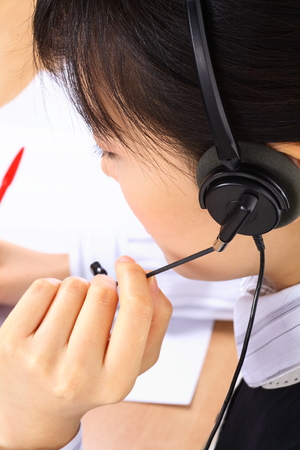 Back shot of a female telemarketer holding a mic of the headset Stock Photo