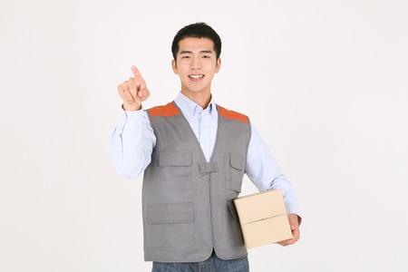 Een bezorger die met de wijsvinger wijst en een doos met verzending vasthoudt Stockfoto
