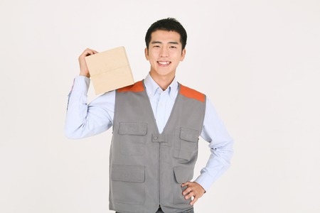 A delivery man holding a box on a shoulder as putting the other hand on waist Stock fotó