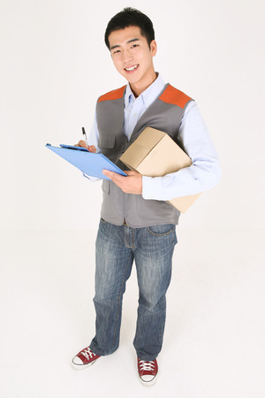 A delivery man writing down on a chart as holding a box of shipment in arm Stock Photo