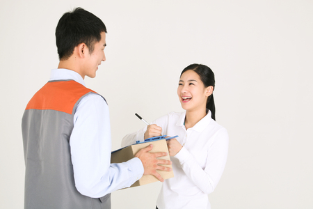 A delivery man holding a shipment while a female recipient signing on the sheet