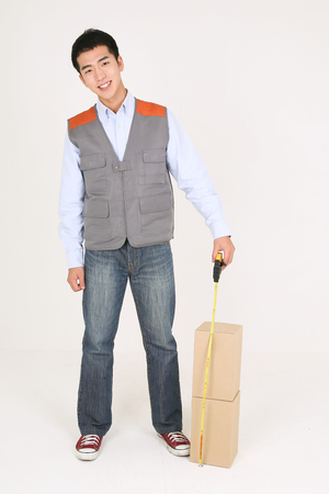 A delivery man measuring boxes as standing straight Stock Photo