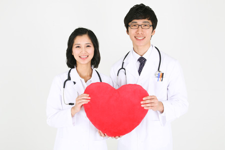 Close up shot of a couple of doctors holding a big heart shape together as standing