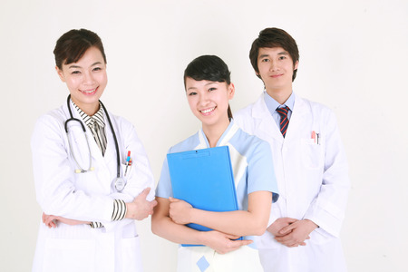 figuring: Close up shot of A female doctor and nurse holding a patient chart standing in front of a male doctor