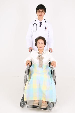 車椅子に座っている先輩患者の後ろに立って男性医師