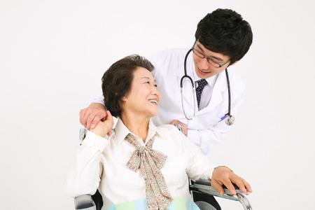 車椅子に座っている先輩患者で男性医師 eyecontacting