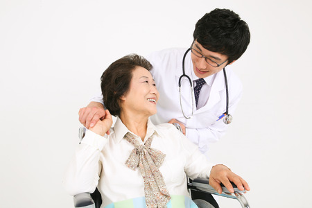 A male doctor eyecontacting with the senior patient sitting in wheelchair Imagens