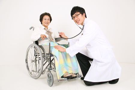 Full body shot of a male doctor applying a stethoscope on a senior patient sitting in wheelchair Stock Photo