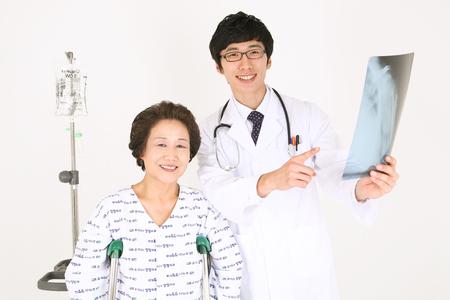 Sluit omhoog geschoten van een mannelijke arts die een x-ray foto met een hogere patiënt houdt die zich op steunpilaren bevindt Stockfoto