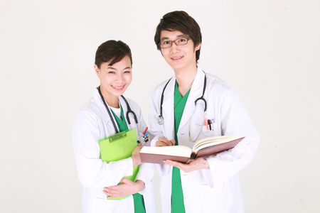 md: Close up shot of A couple of surgeon looking at a chart and a book together as stethoscopes around the neck