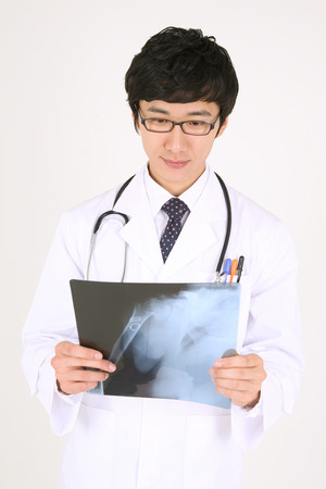 Close up shot of a male doctor thinking deeply as looking at an x-ray photographs Stock Photo