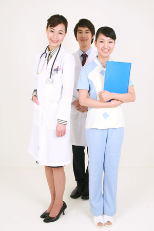 Full shot of A male doctor standing behind the female doctor and nurse Stock Photo