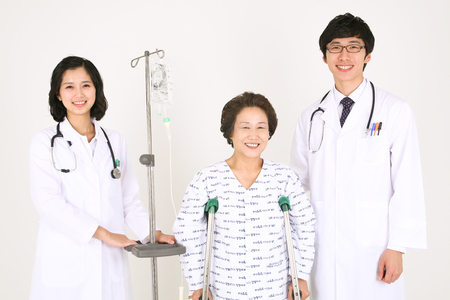 kind hearted: Close up shot of a couple of doctors standing with a senior patient standing on crutches Stock Photo