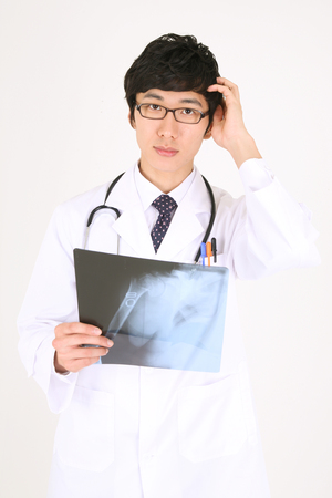 figuring: A male doctor scratching his head as looking at an x-ray photographs