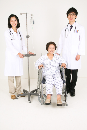 A couple of doctors standing around the senior patient sitting in wheelchair Stock Photo