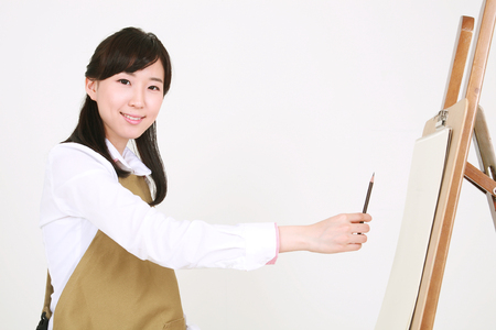 Close up shot of a female artist drawing with a pencil sitting in front of the easel Stock Photo