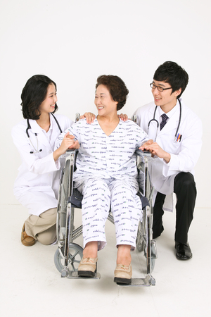 kind hearted: A couple of doctors putting hands on shoulders of the senior patient Stock Photo
