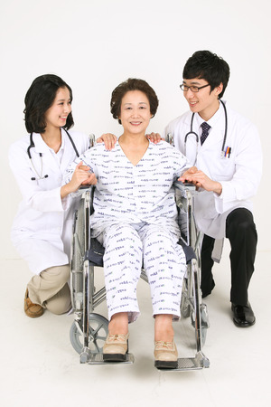 sholders: A couple of doctors putting hands on shoulders of the senior patient Stock Photo