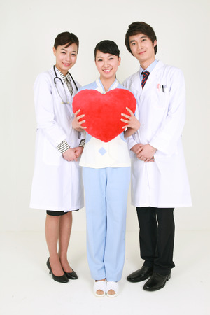 Full shot of A female nurse holding a heart shaped cushion as standing between a male doctor and a female doctor