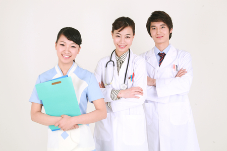 Close up shot of A male doctor, female doctor and nurse standing in a row with a patient chart Stock Photo