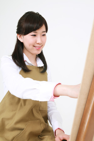 A female artist drawing with a pencil sitting in front of the easel Stock Photo